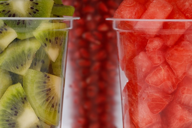 Fette di anguria, melograno e kiwi disposte in due bicchieri trasparenti con fondo bianco, isolato