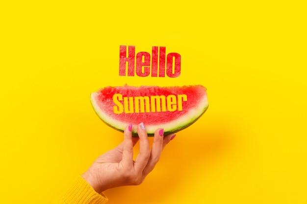 Fetta di anguria in mano con scritta ciao estate