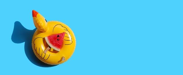 Ghiacciolo della fetta dell'anguria sul gonfiabile dell'anatra gialla sulla superficie blu