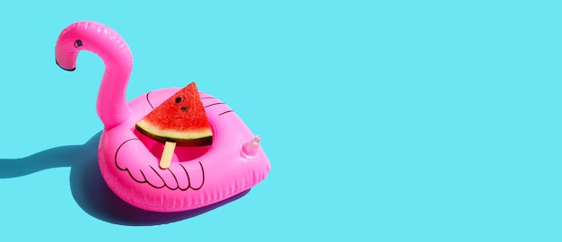 Ghiacciolo di fetta di anguria con gonfiabile di fenicottero rosa sulla superficie blu