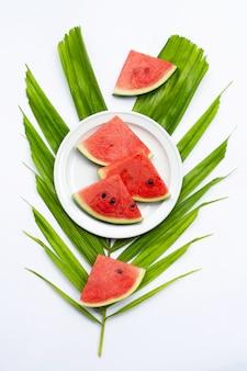 Fette di anguria su foglia di palma tropicale su bianco