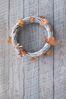 Corona dell'acacia con le foglie di autunno asciutte su legno con lo spazio del testo