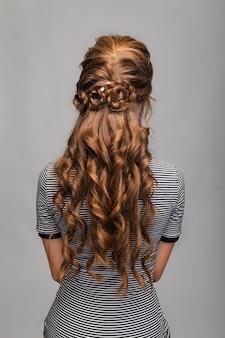 Acconciatura con riccioli ondulati. acconciatura su donna capelli castani rossi con capelli lunghi su sfondo grigio.