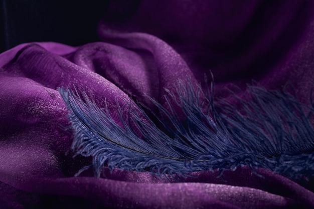 Onda di elegante trama tessile viola con belle piume blu. sfondo bello, delicato e gentile
