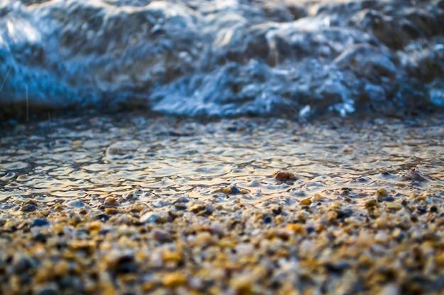 Onda vicino alla riva un litorale di sabbia fine insieme a ciottoli