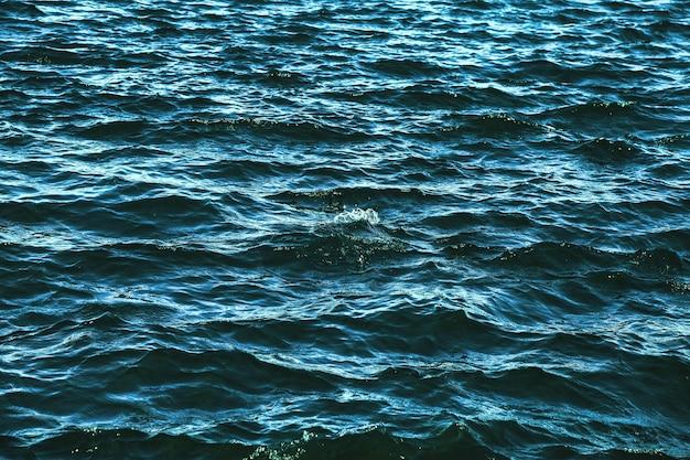 Superficie del modello di onda fresca o serbatoio di mare. sfondo di onde del fiume che lambiscono sulla superficie dell'acqua mare o onde dell'oceano. sfondi natura sfondi concetto. foto increspature del lago. copia spazio