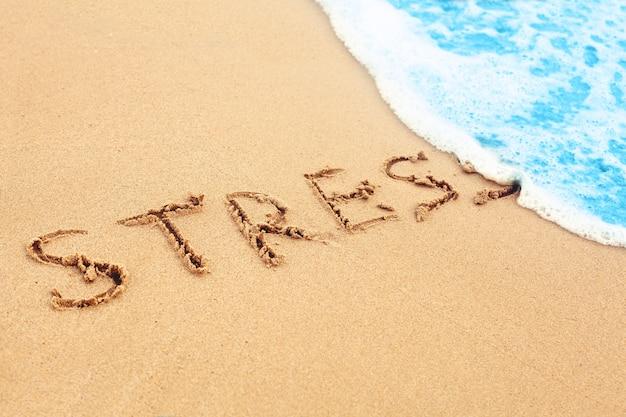 Onda sulla spiaggia del mare lava via lo stress del segno sulla sabbia