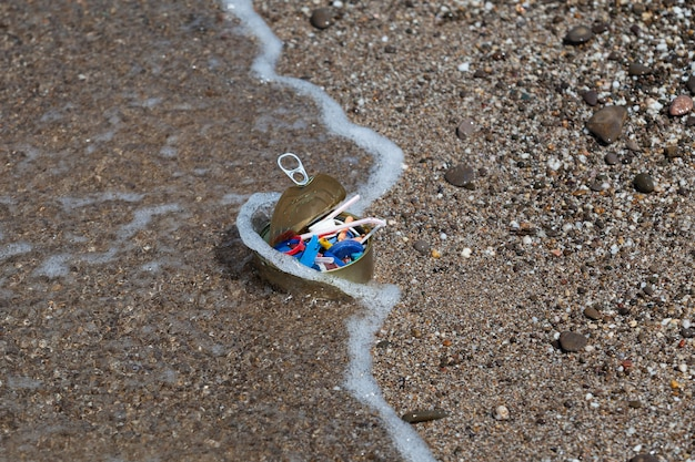 L'onda lancia un barattolo di latta pieno di plastica che galleggia nel mare sulla riva inquinamento ambientale