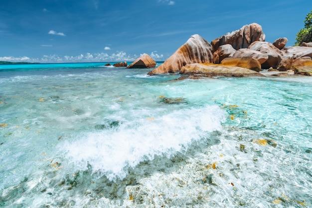 Onde di anse cocos all'isola di la digue, seychelles. bella spiaggia tropicale isolata con rocce nell'oceano.