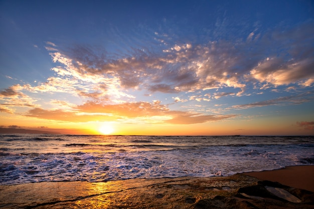 Onde che si infrangono sulle rocce dopo il tramonto vicino alla spiaggia al tramonto, oahu, hawaii