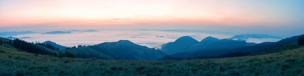 Onde di nuvole sopra le montagne al mattino