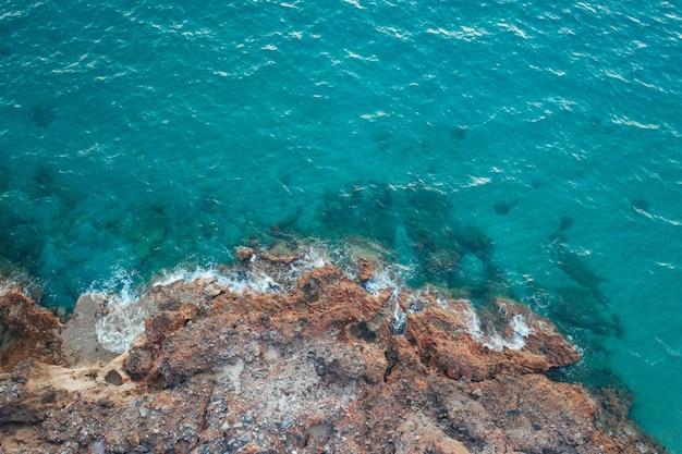 Onde del mar mediterraneo che si infrangono contro gli scogli
