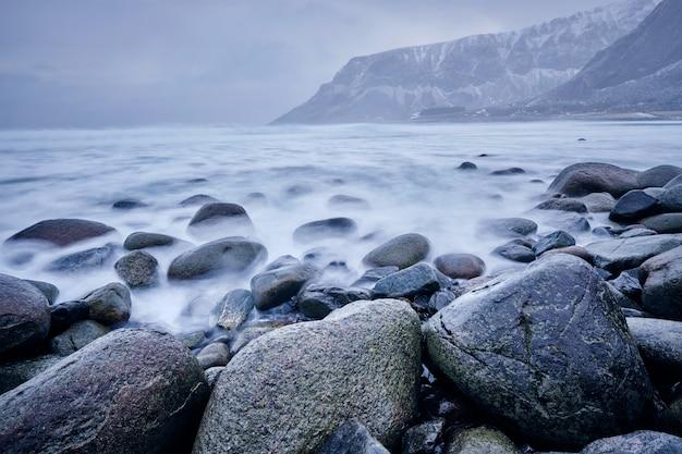 Onde del mare di norvegia che si innalzano su rocce di pietra. esposizione prolungata