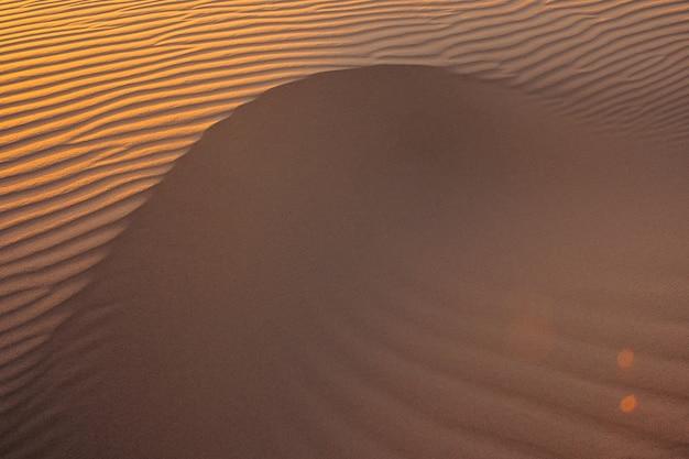 Onde di texture di sabbia. dune del deserto al tramonto. belle strutture di barkhan sabbiosi.