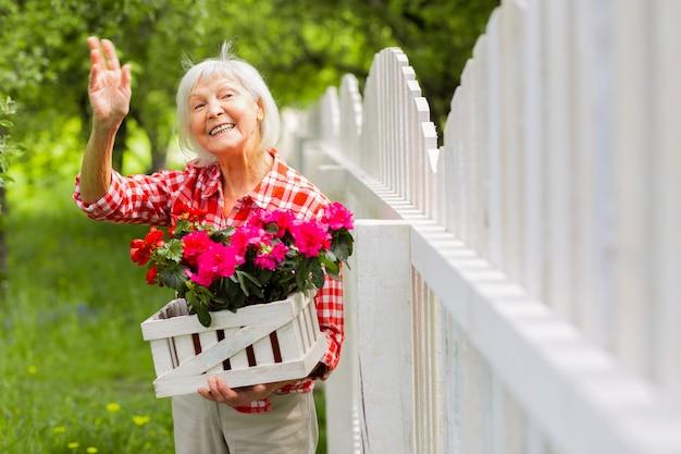 Salutando il vicino. raggiungendo la bella signora anziana che saluta il suo vicino in piedi vicino al recinto