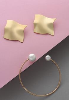 Coppia di orecchini a forma ondulata e bracciale con perla su carta rosa e grigia