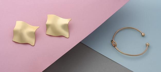 Coppia di orecchini a forma ondulata e bracciale a forma di nodo su sfondo di carta in colori pastello
