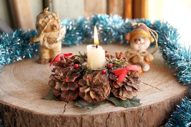 Candela di cera su supporto decorativo da coni