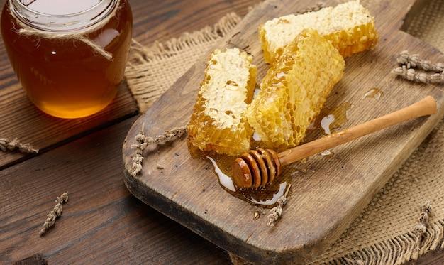 Favo di cera con miele su una tavola di legno, dietro un barattolo di miele, vista dall'alto
