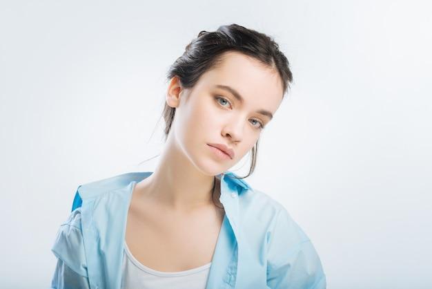 Modo di sognare. meditativa bella donna carina vestirsi in camicia mentre abbassa la testa sulla spalla e guarda la telecamera