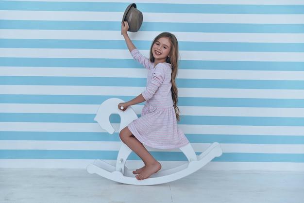 Sulla strada per il suo mondo dei sogni. bambina sveglia che saluta con il suo cappello e guarda la telecamera con un sorriso