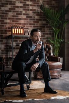 Modo per rilassarsi. uomo barbuto brutale bello che tiene un bicchiere di whisky e lo beve mentre era seduto sul tavolino