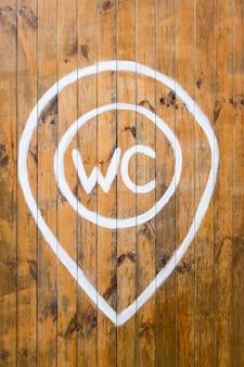 Segno di wc con testo dipinto di bianco sulla parete in legno.