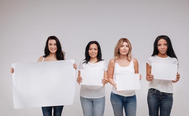 Siamo tutti umani. meravigliose signore senza paura attraenti in piedi l'una vicino all'altra e tenendo poster in bianco mentre posano