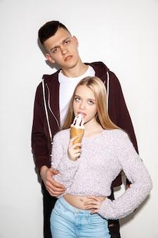 Siamo amici. chiuda sul ritratto di moda di due giovani hipster cool ragazza e ragazzo che indossa jeans indossano. due modelli che si divertono e fanno facce buffe.