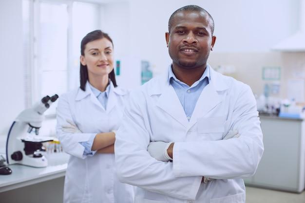 Siamo felici. ha ispirato ricercatori di successo che indossano uniformi e stanno in piedi nel laboratorio