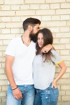 Siamo solo una coppia innamorata l'uno dell'altra. coppie amorose che abbracciano sul muro di mattoni. coppia familiare di uomo barbuto e donna sexy. coppia sensuale in stile casual.