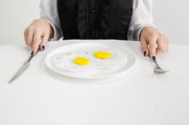 Siamo quello che mangiamo. chiuda in su della donna che mangia uova fritte di plastica, concetto di eco. ci sono così tanti polimeri che ne siamo fatti. disastro ambientale, moda, bellezza. perdere il mondo organico.