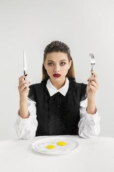 Siamo quello che mangiamo. donna che mangia uova fritte di plastica, concetto di eco. ci sono così tanti polimeri che ne siamo fatti. disastro ambientale, moda, bellezza, cibo. perdendo il mondo organico.