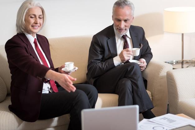 Ci piace il processo di discussione. allegra imprenditrice invecchiata felice sorridente e seduto in ufficio mentre beve un caffè con il suo collega e indica il computer portatile sul tavolo