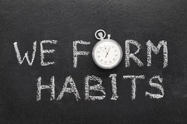 Formiamo una frase di abitudini scritta a mano sulla lavagna con un cronometro vintage preciso usato al posto della o