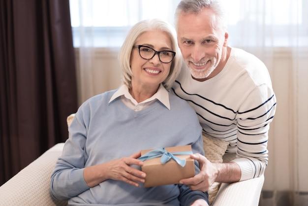 Siamo felici insieme. coppie invecchiate sorridenti allegre che tengono un regalo mentre sedendosi sul divano ed esprimendo felicità