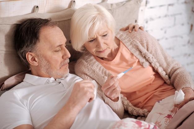 Abbiamo la febbre. vista dall'alto della coppia di anziani sdraiata sul letto e controllare il tempo sul termometro.