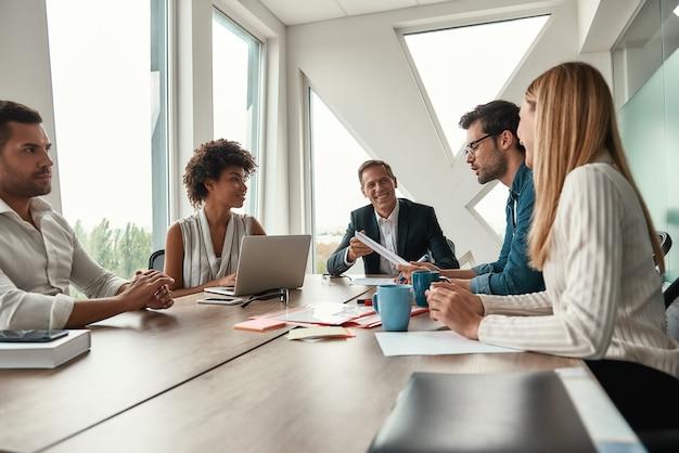 Abbiamo ottimi risultati. team multiculturale che discute un nuovo progetto e sorride mentre è seduto al tavolo dell'ufficio. brainstorming