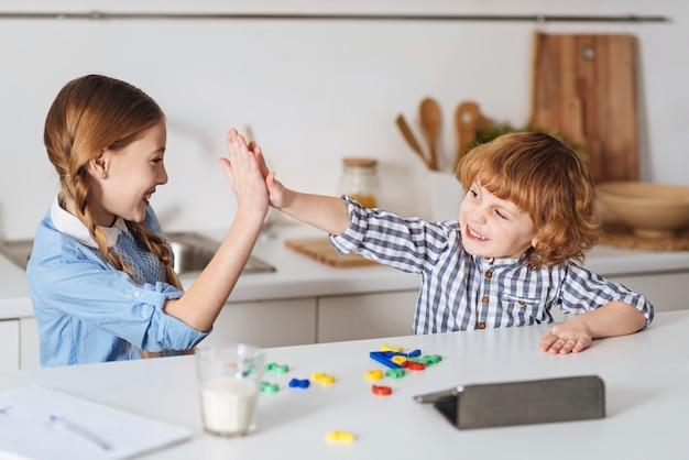 Siamo una grande squadra. bambini intelligenti, dolci ed entusiasti che svolgono un compito di matematica utilizzando un gioco speciale mentre si divertono in cucina al mattino