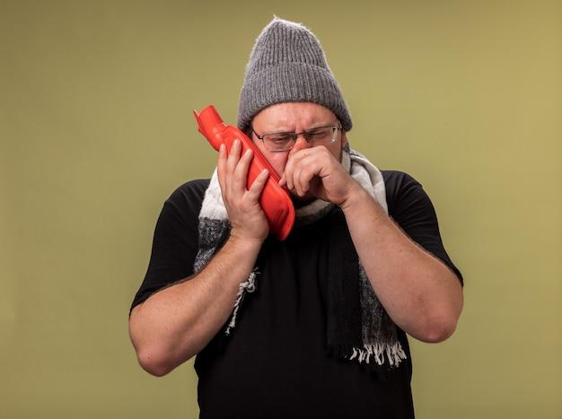 Debole maschio malato di mezza età che indossa cappello invernale e sciarpa mettendo la borsa dell'acqua calda sulla guancia asciugandosi il naso con la mano