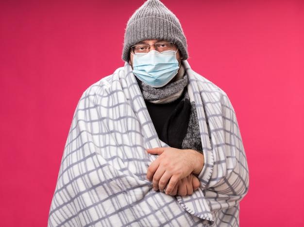 Debole maschio malato di mezza età che indossa cappello invernale con sciarpa e maschera medica avvolta in plaid isolato su parete rosa