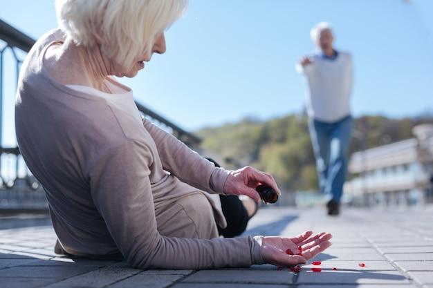 Debole vecchia donna paurosa in piedi bisognosa di pillole che sente dolore nel suo corpo mentre passa un pedone che si affretta a salvare questa signora