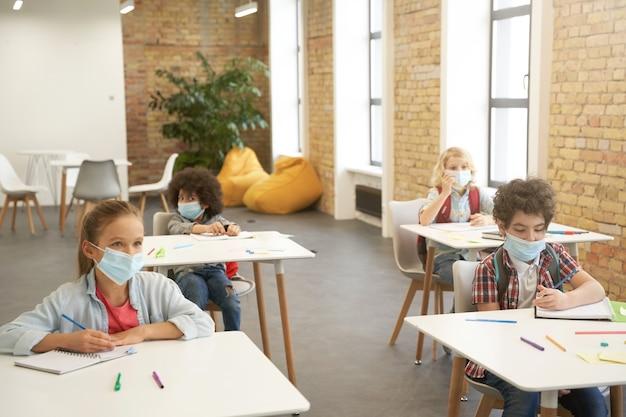 Indossare rivestimenti per il viso all'interno dei bambini delle scuole che indossano una maschera protettiva durante l'epidemia di coronavirus