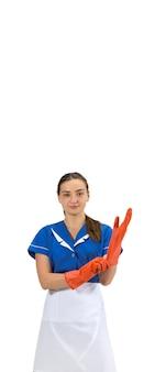 Indossare guanti. ritratto di donna fatta, cameriera, addetta alle pulizie in uniforme bianca e blu isolata su bianco