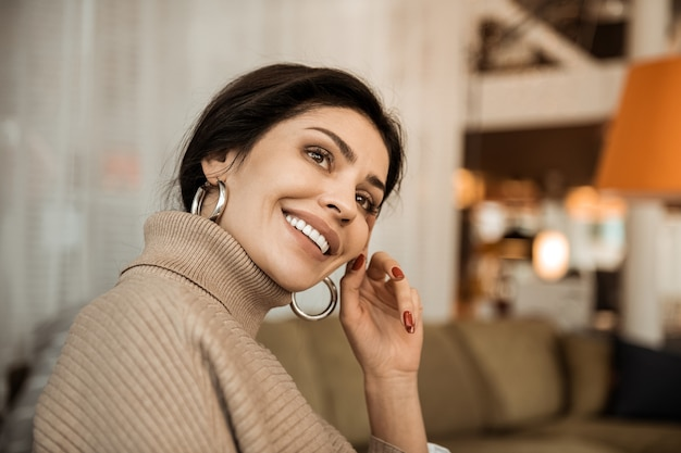 Indossare orecchini d'oro. attraente signora raggiante con i capelli scuri pensieroso seduto sul divano e toccando il suo viso ordinato