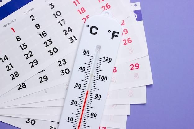 Termometro meteorologico con un calendario mensile su un viola
