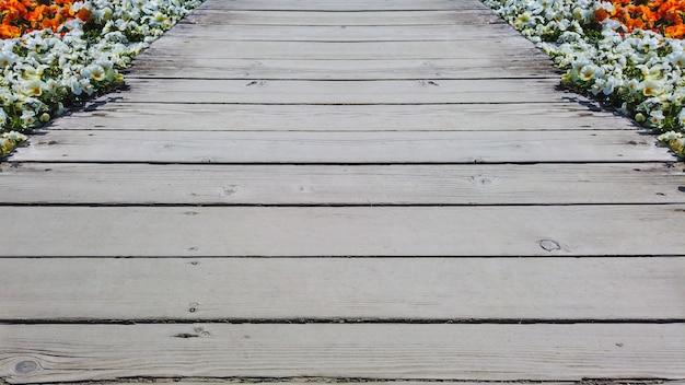 Vecchio percorso di modo di camminata di legno stagionato della pavimentazione fra il giardino di fiori.