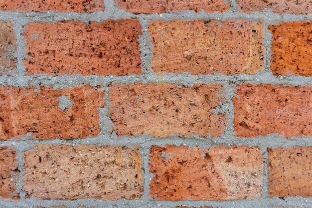 Vecchio fondo del muro di mattoni macchiato esposto all'aria