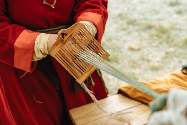 Mestiere di tessitura. la donna in abito tradizionale lavora con le mani