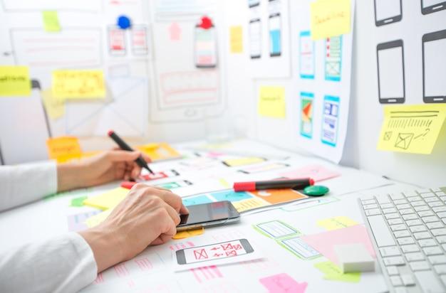 Web designer sta sviluppando un'applicazione per telefoni cellulari. creazione di un layout delle funzioni dell'interfaccia utente degli smartphone.